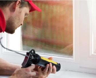 man caulking a window