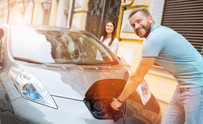 Man unplugging the charger from his electric car