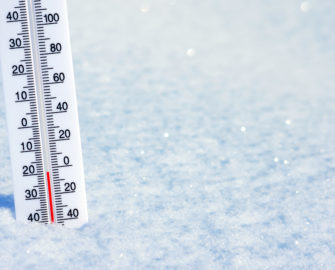 thermometer reading negative 3 degrees Fahrenheit sitting in snow