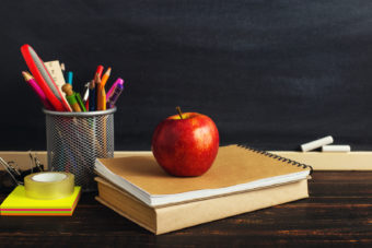 Teacher's desk with writing materials, a book and an apple, a blank for text or a background for a school theme.