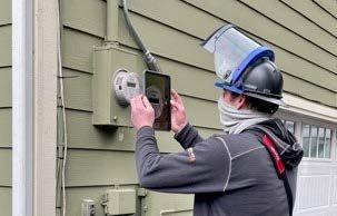 Penlight worker replacing meter on side of house