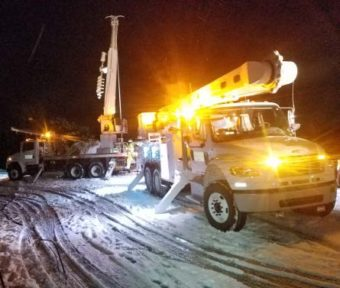 bucket truck outside at night in the snow