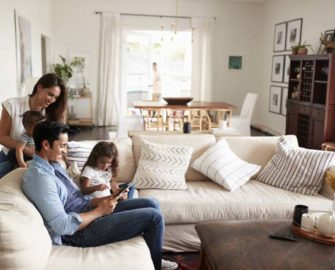 family in living room with dad looking at tablet