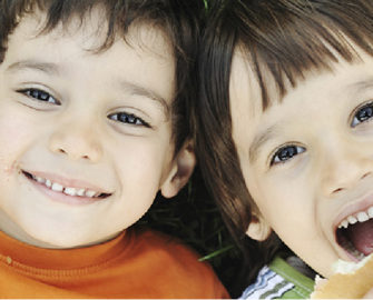 Two smiling children hold sandwiches