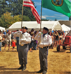 Two men hold a US flag and a Washington state flag. Tents, a crowd, and a tractor are seen in the background