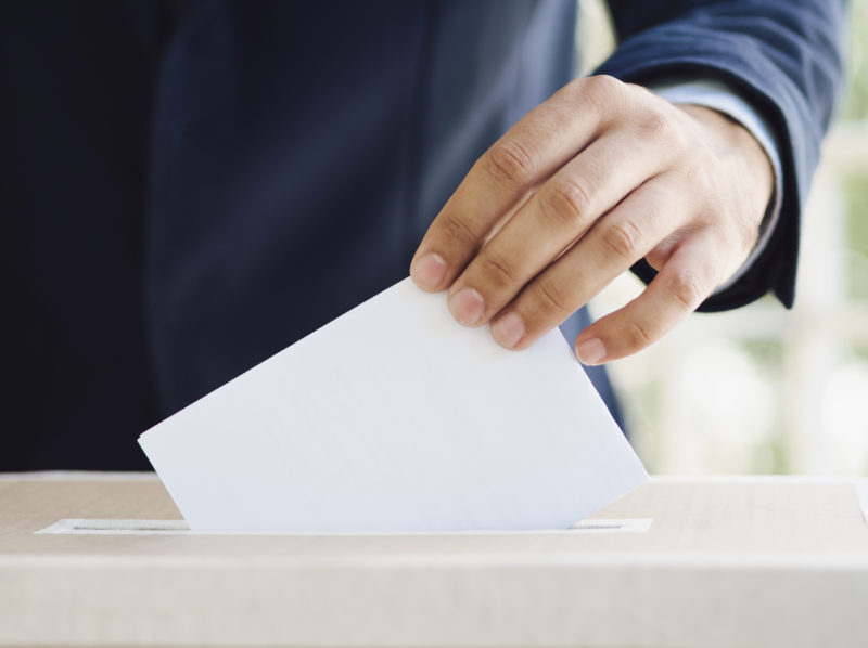 Man putting an empty ballot in election box