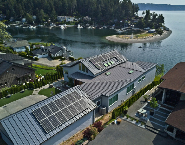An aerial photo shows a home with multiple solar panels on the roof. A bay is seen in the background.