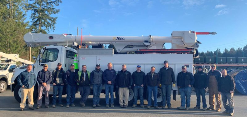 Peninsula light staff/lineworkers in front of a truck