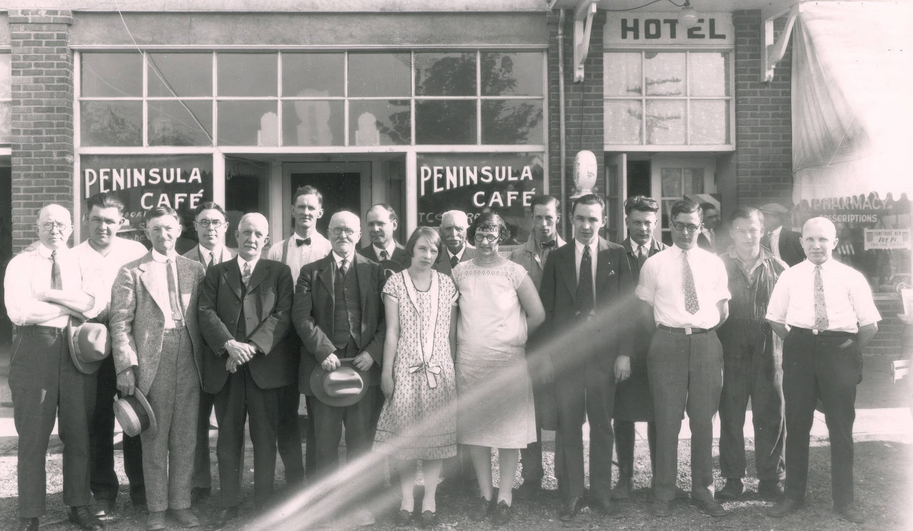 black and white photo of large group of people in front of PenLight staff in front of office building
