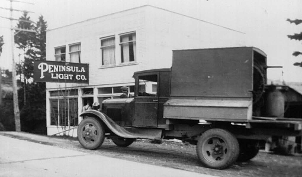 black and white photo of truck in front of Peninsula light co office