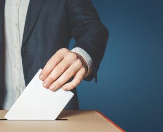 a person placing an envelope into a ballot box