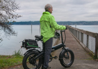 Man with electric bicycle nearby a dock platform