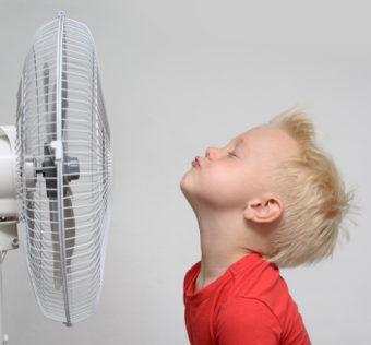 A little boy standing in front of a fan