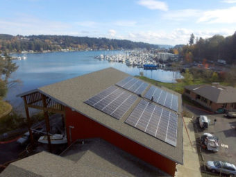 Solar panels on a building next to a lake