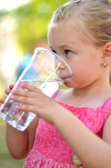 child drinking a cup of water