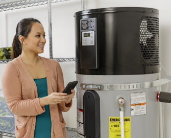Woman holding cell phone and looking at water heater