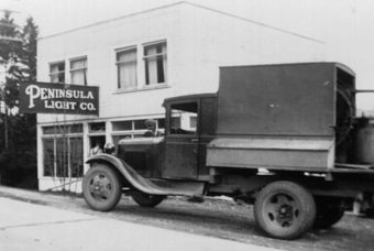 Black and white photo of a truck outside of Peninsula Light Co